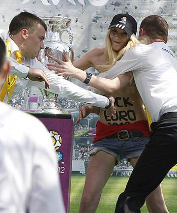 Security guards detain a demonstrating activist from women's rights organisation Femen near the Euro 2012 trophy during its unveiling to the public in central Kyiv.