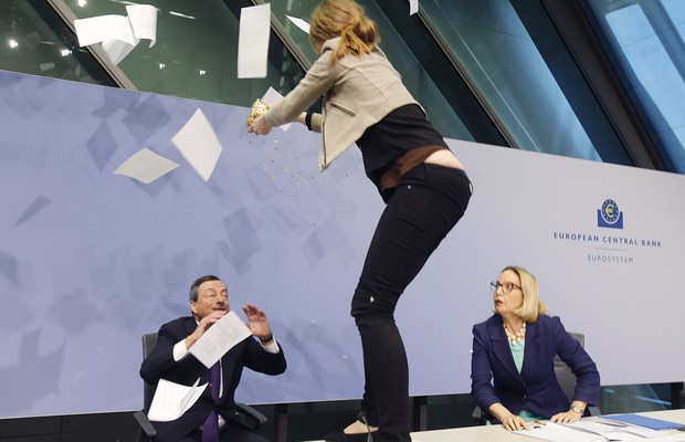 ADDS NAME OF THE WOMAN AT RIGHT - An activist stands on the table of the podium throwing paper at ECB President Mario Draghi, left, as Christine Graeff, Director General of Communications, looks on during a press conference of the European Central Bank, E (Foto: AP)