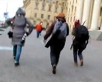 Journalists run from the scene after security officers appear.