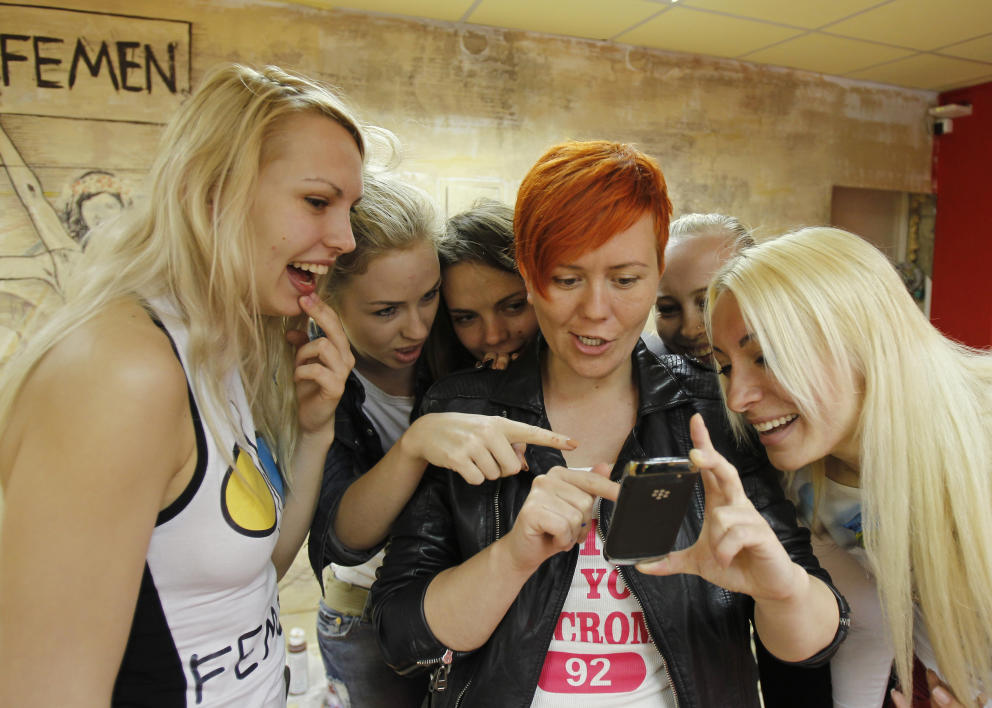 Anna Hutsol, fundadora de Femen en Ucrania (c), muestra a otras mujeres imágenes de una protesta en su sede en Kyiv (Reuters).