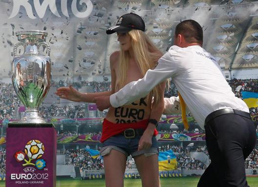 Eine Aktivistin von FEMEN, mit einem Anti-Euro Slogan auf dem Bauch, versucht den UEFA-Pokal, der auf dem Unabhängigkeitsplatz in Kiew präsentiert wird, zu berühren. Ein Sicherheitsbeamter versucht sie zu stoppen. Foto: dpa