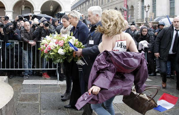 Militantes do grupo feminista Femen interrompem discurso da presidente do partido de extrema-direita Frente Nacional, Marine Le Pen (centro), com escritos 'Le Pen top facista' no peito  (Foto: Francois Mori/AP)